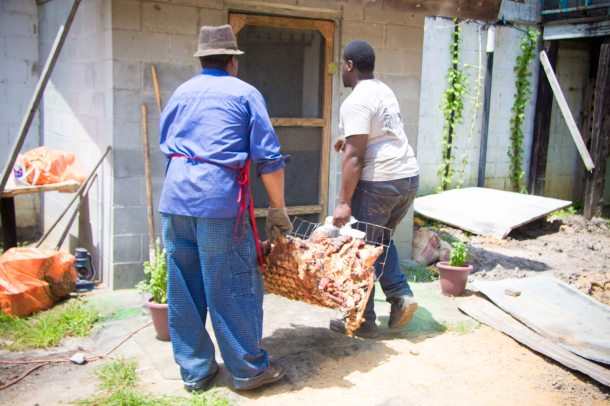 The cooked hog being taken into the back of the kitchen to be taken apart.