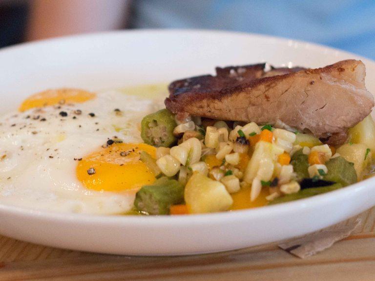 Braised pork belly with  Braised pork belly with stewed corn & charred okra, cherry tomatoes, polenta, sunnyside farm eggs, chili oil